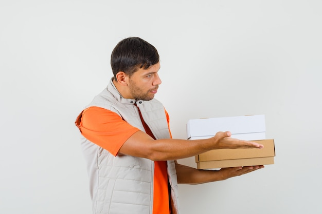 Young male in t-shirt, jacket welcoming while holding cardboard boxes and looking gentle , front view.