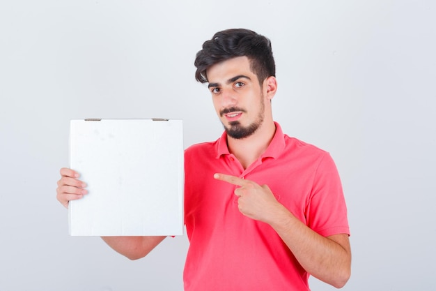 Young male in t-shirt pointing pizza box and looking joyful , front view.