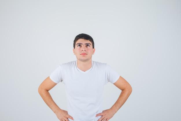 Giovane maschio in maglietta in posa con le mani sulla vita e guardando pensieroso, vista frontale.