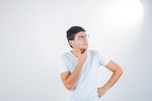 Giovane maschio in maglietta che mostra nella posa di pensiero e guardando premuroso, vista frontale.