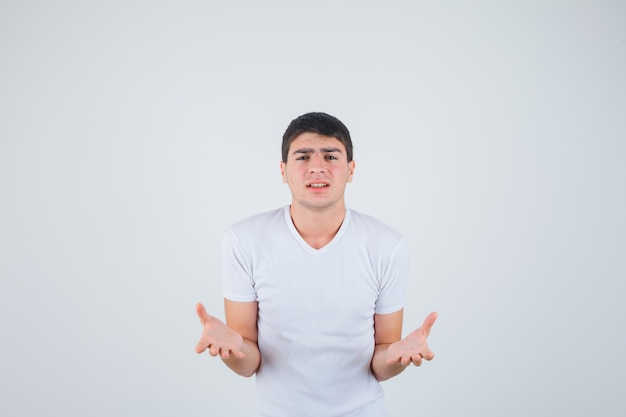 Young male in t-shirt stretching hand in questioning gesture and looking excited , front view.