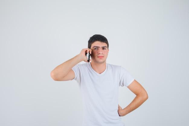Giovane maschio in t-shirt parlando al telefono cellulare e guardando fiducioso, vista frontale.
