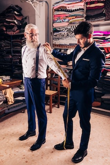 Young male tailor taking measurement of senior man's sleeves in the shop