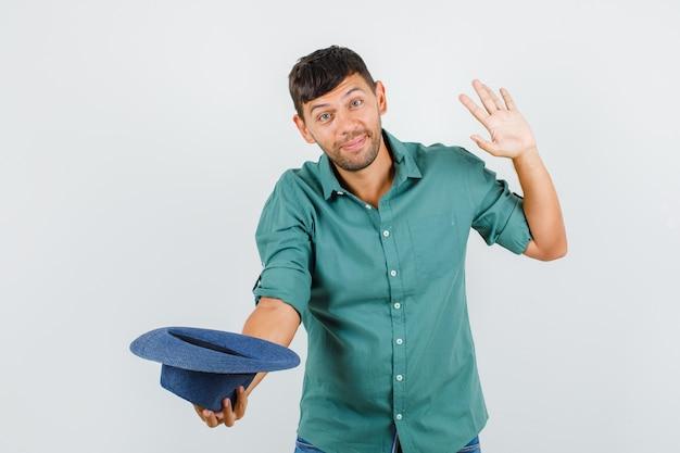 젊은 남성 셔츠에 손을 흔들며 쾌활한 찾고있는 동안 모자를 벗고
