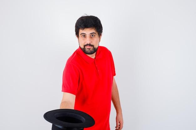 빨간 t- 셔츠 전면보기에서 누군가와 회의하는 동안 그의 모자를 벗고 젊은 남성.