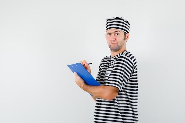 T- 셔츠, 모자에 클립 보드에 메모를 복용 하 고 잠겨있는 찾고 젊은 남성.