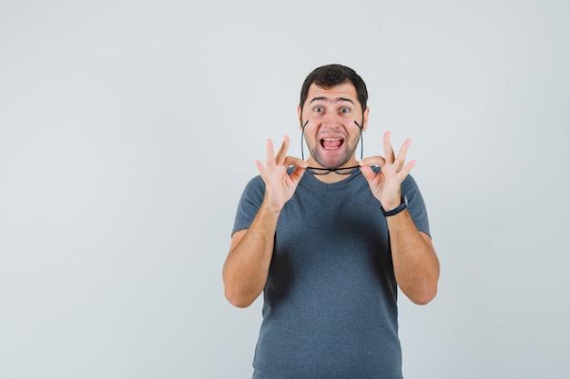 Молодой мужчина снимает очки в серой футболке и выглядит счастливым