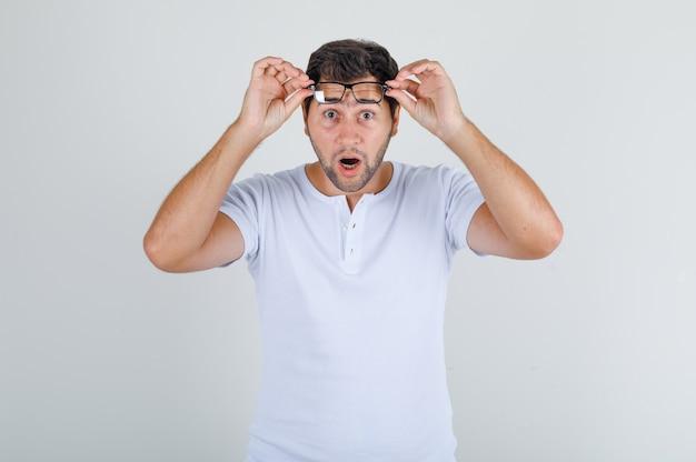 흰색 t- 셔츠에 안경을 벗고 충격을 찾고 젊은 남성