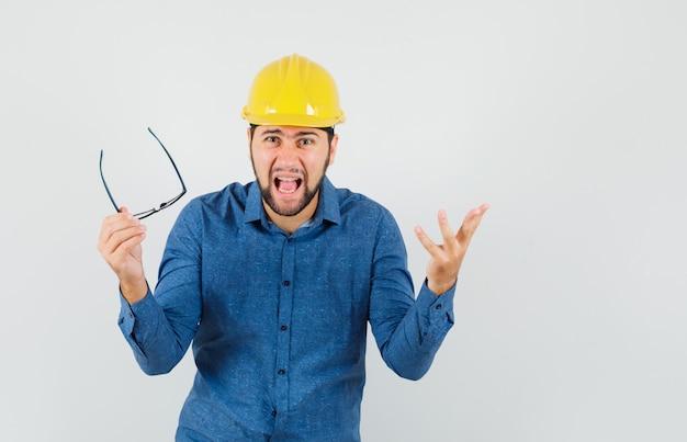 Giovane maschio che toglie gli occhiali mentre urla in camicia