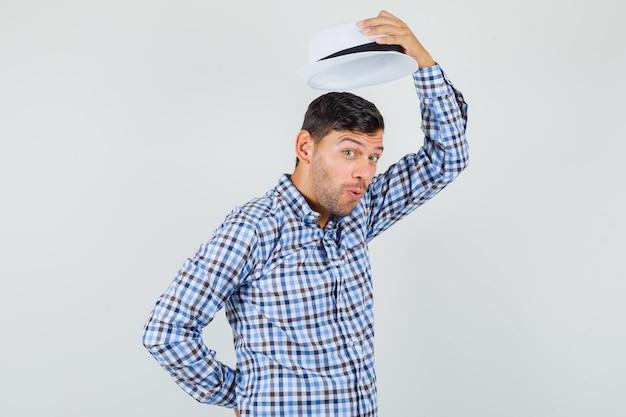 체크 셔츠에 그의 모자를 벗고 기뻐 보이는 젊은 남성