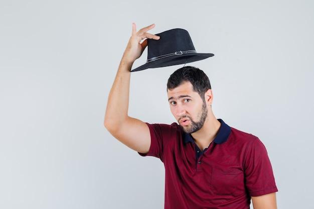 Giovane maschio che si toglie il cappello in maglietta rossa, vista frontale.