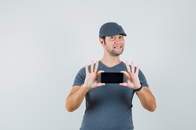Молодой мужчина фотографирует на мобильном телефоне в кепке футболки и выглядит весело