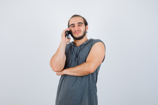 Young male talking on mobile phone in sleeveless hoodie and looking handsome. front view.