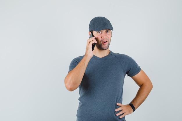 Giovane maschio che comunica sul telefono cellulare in protezione della maglietta e che osserva stupito