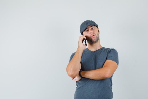 Giovane maschio che comunica sul telefono cellulare in protezione della maglietta e che sembra esitante