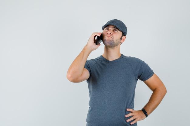 Giovane maschio che comunica sul telefono cellulare in protezione della maglietta e che sembra pensieroso