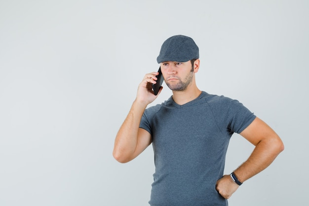 Young male talking on mobile phone in t-shirt cap and looking sad