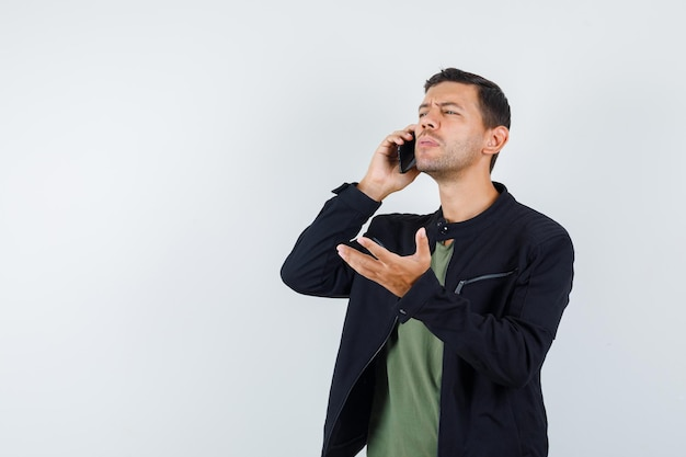 Young male talking on mobile phone in t-shirt, jacket front view.