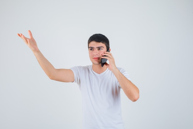 Young male talking on mobile phone while raising arm in t-shirt and looking excited. front view.