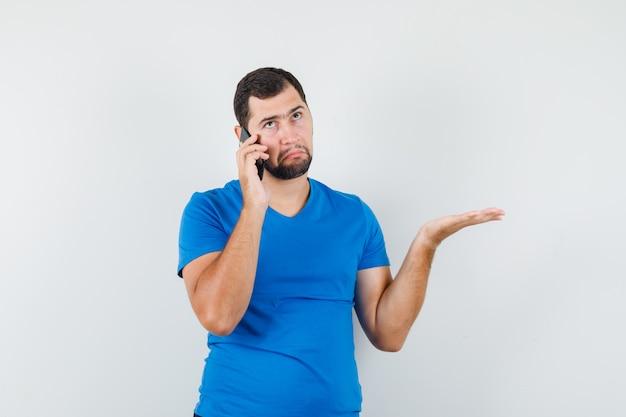 青いtシャツを着て携帯電話で話し、混乱しているように見える若い男性
