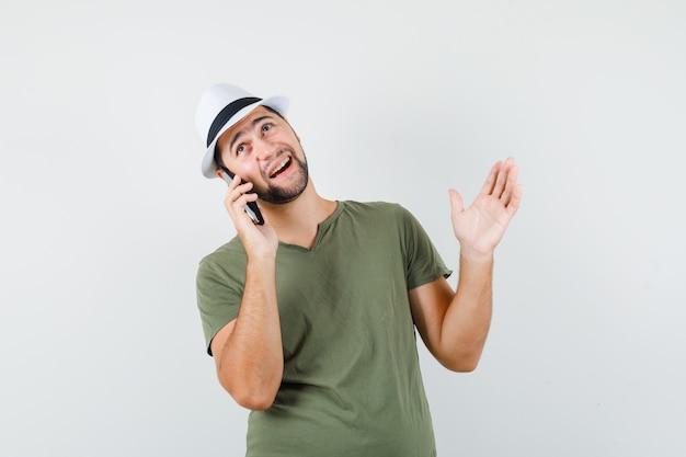 緑のtシャツと帽子で携帯電話で話し、陽気に見える若い男性
