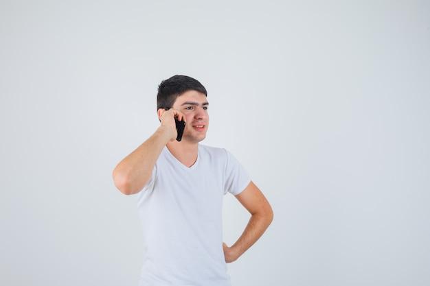 Tシャツを着て携帯電話で話し、陽気に見える若い男性。正面図。