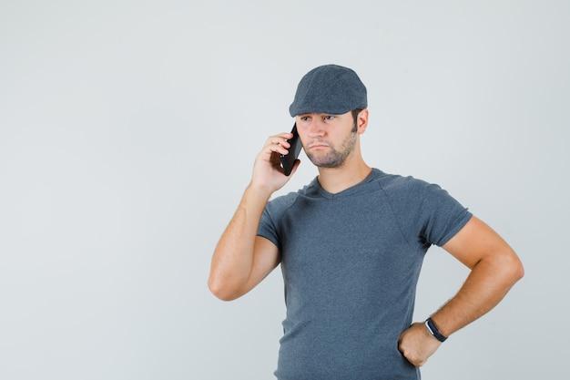 Молодой мужчина разговаривает по мобильному телефону в кепке футболки и выглядит грустно