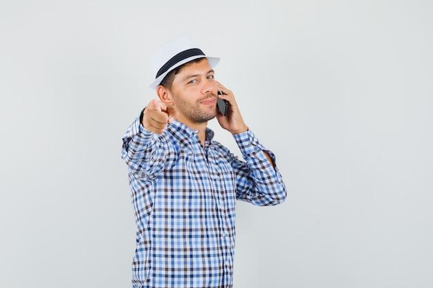 체크 셔츠에 카메라를 가리키는 휴대 전화에 말하는 젊은 남성