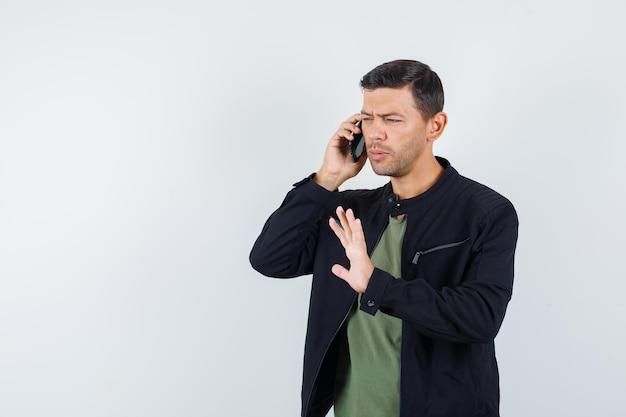젊은 남성은 티셔츠, 재킷 전면 보기에서 정지 제스처와 함께 휴대 전화로 이야기합니다.