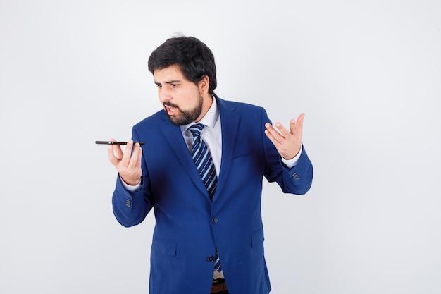 シャツ、ジャケット、ネクタイ、正面図で電話で話している若い男性。