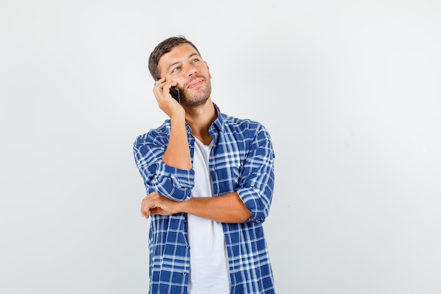 Young male talking on smartphone while looking up in shirt and looking pensive , front view.