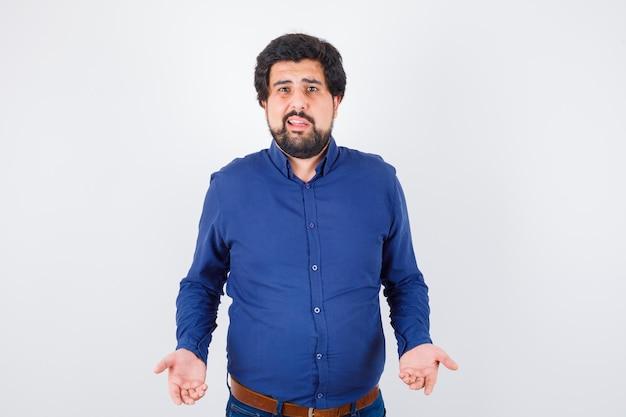 ロイヤルブルーのシャツの正面図で誰かと話している若い男性。