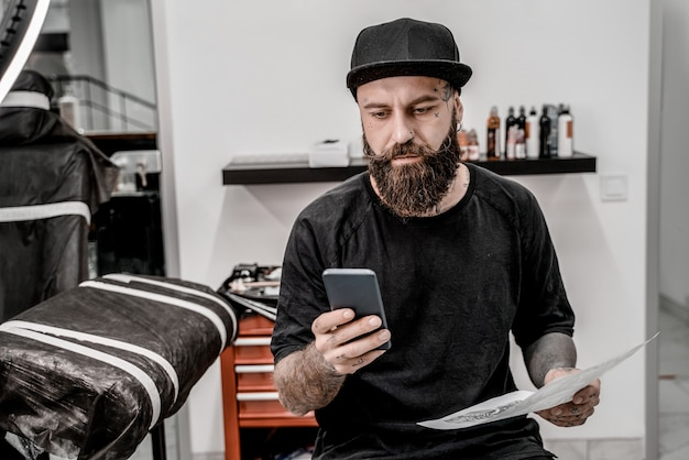 Young male tattoo artist with beard holding phone and sketch sitting on couch in workshop place.