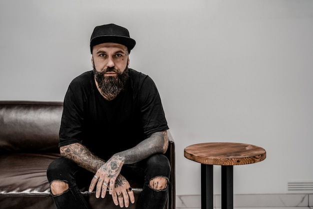 Young male tattoo artist with beard looks serious sitting on couch in workshop place.