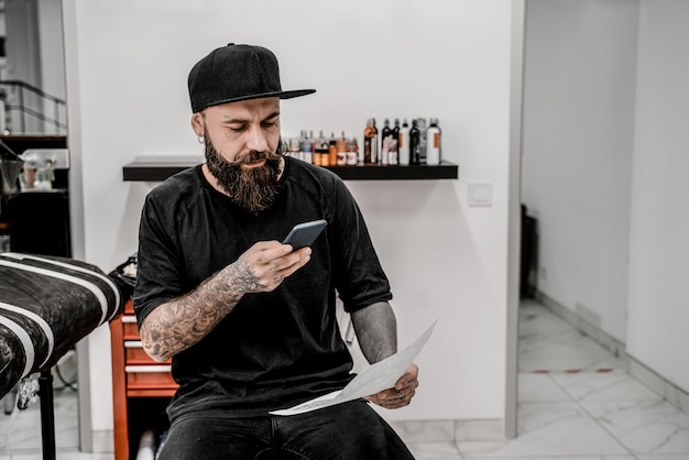 Young male tattoo artist with beard taking picture of sketch sitting on couch in workshop place.
