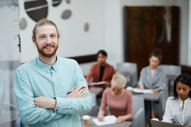 Young male teacher posing by board