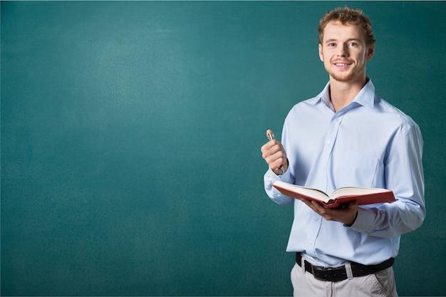 本を持って立っている若い男性教師