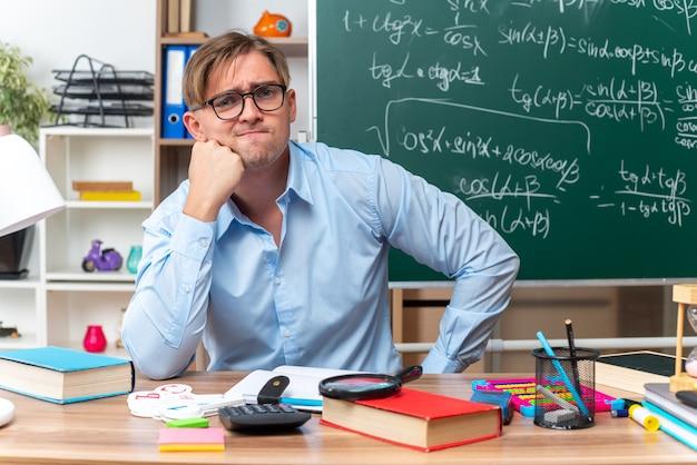Giovane insegnante maschio con gli occhiali confuso e molto ansioso seduto al banco di scuola con libri e appunti davanti alla lavagna in classe