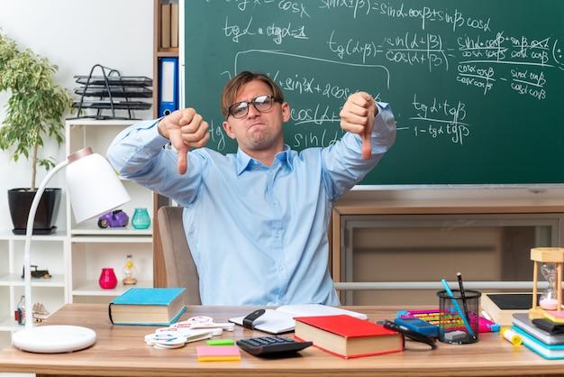 Giovane maschio insegnante con gli occhiali dispiaciuto che mostra il pollice verso il basso seduto al banco di scuola con libri e note davanti alla lavagna in aula