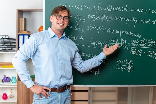 Giovane insegnante maschio con gli occhiali che spiega la lezione felice e sorridente in piedi vicino alla lavagna con formule matematiche in classe