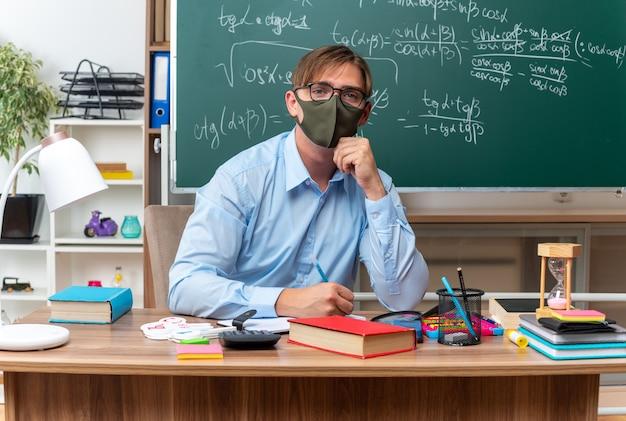 Giovane insegnante maschio con gli occhiali e maschera protettiva per il viso che guarda l'obbiettivo con faccia seria seduto al banco di scuola con libri e note davanti alla lavagna in aula