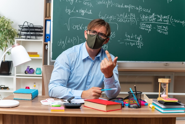 Young male teacher wearing glasses and facial protective mask looking confused raising arm in displeasure sitting at school desk with books and notes in front of blackboard in classroom