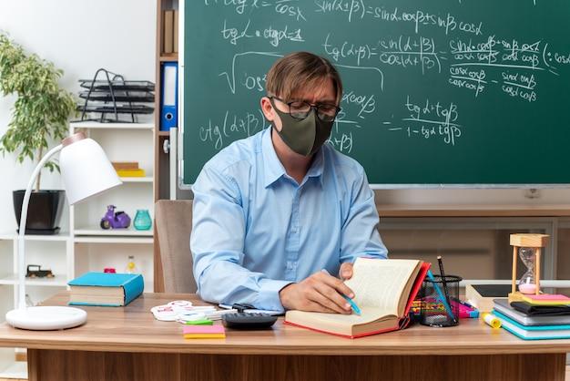 Giovane insegnante maschio che indossa occhiali e maschera protettiva facciale preparando la lezione che sembra sicuro seduto al banco di scuola con libri e note davanti alla lavagna in aula