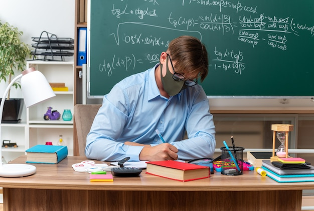 Young male teacher wearing glasses and facial protective mask preparing lesson looking confident sitting at school desk with books and notes in front of blackboard in classroom