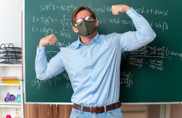 Giovane insegnante maschio che indossa occhiali in maschera protettiva facciale alzando i pugni come un vincitore che sembra sicuro in piedi vicino alla lavagna con formule matematiche in classe