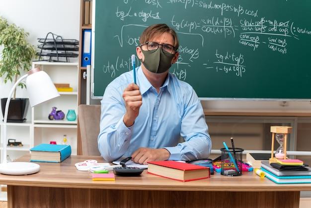 Giovane insegnante maschio che indossa occhiali e maschera protettiva facciale che mostra matita con faccia seria seduto al banco di scuola con libri e note davanti alla lavagna in aula