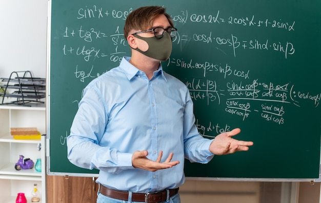 Young male teacher wearing glasses in facial protective mask standing near blackboard with mathematical formulas explaining lesson looking confused in classroom