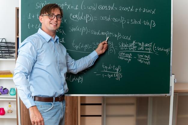 Giovane insegnante maschio con gli occhiali che tiene il gesso che spiega la lezione sorridente fiducioso in piedi vicino alla lavagna con formule matematiche in classe