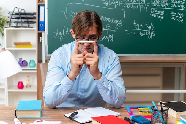 Giovane insegnante maschio con gli occhiali che tiene il gesso guardando con faccia seria seduto al banco di scuola con libri e note davanti alla lavagna in classe