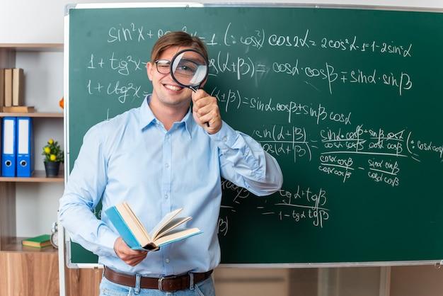 Giovane insegnante maschio che indossa occhiali con lente di ingrandimento e libro felice e positivo spiegando lezione in piedi vicino alla lavagna con formule matematiche in classe